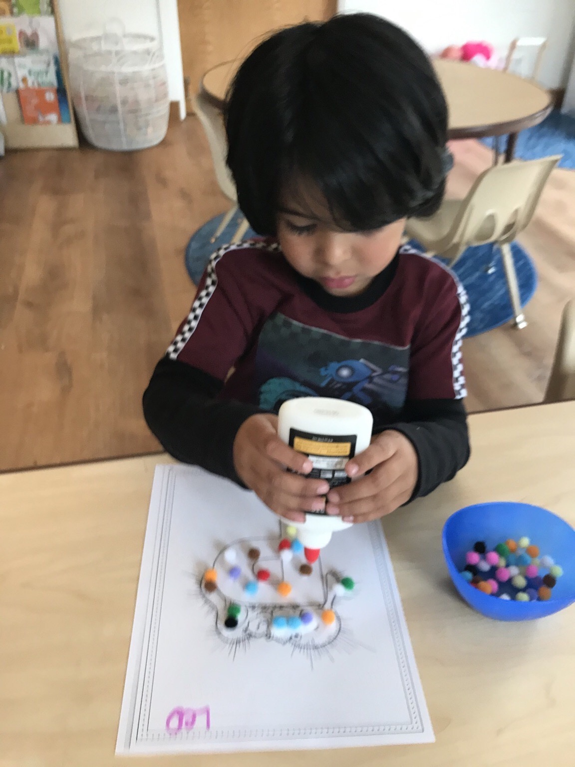 Art - Student gluing beads to drawing