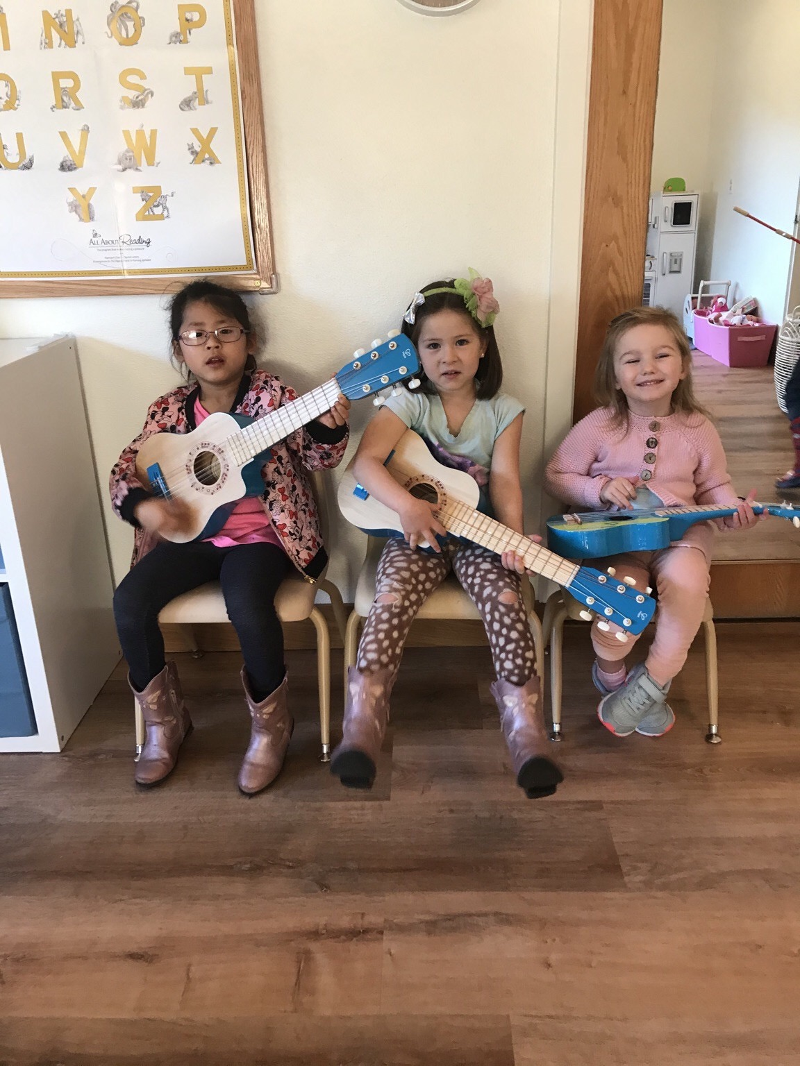 Music - Students sitting on chairs and playing guitars