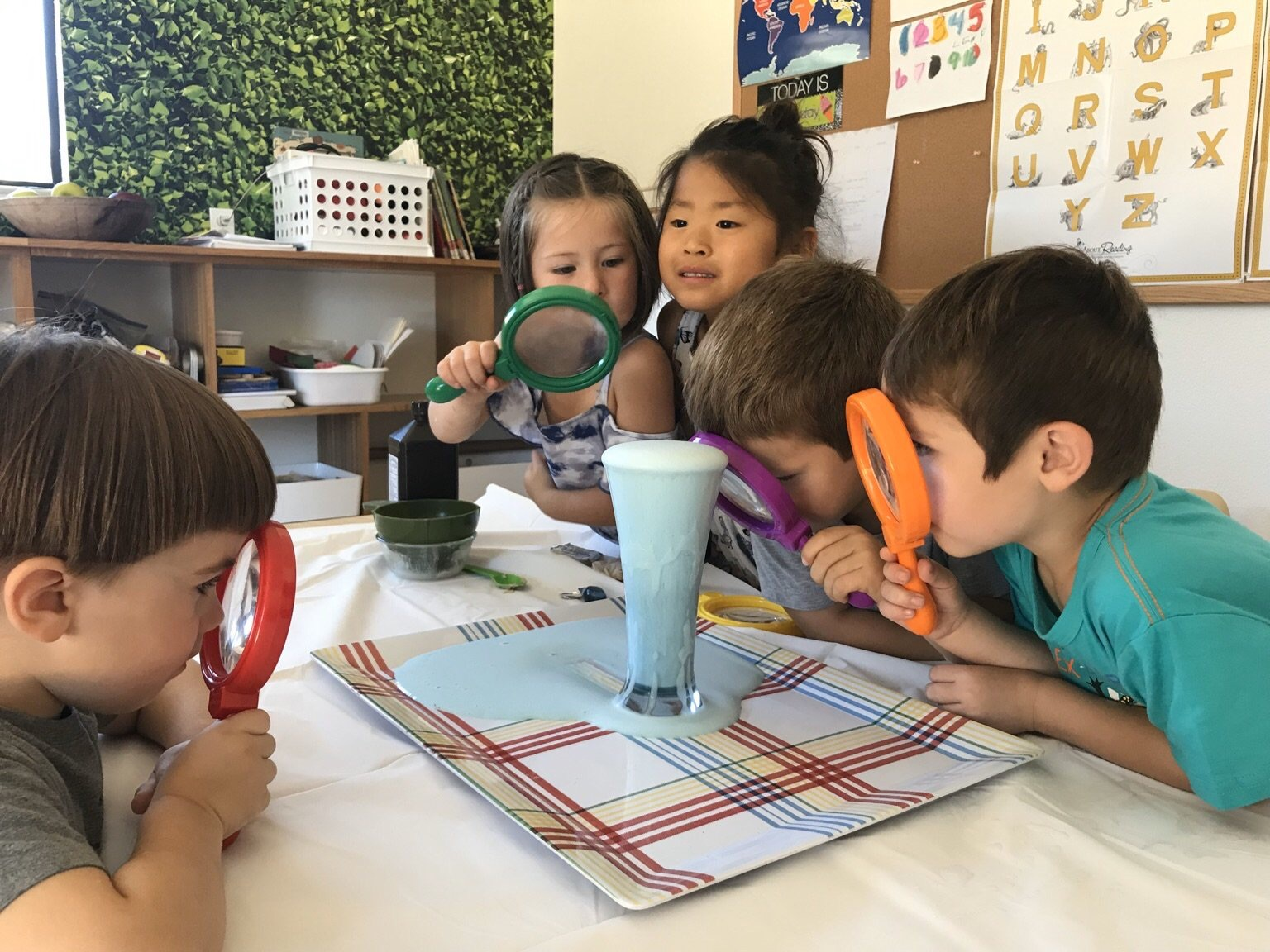 Science - students using magnifying glass to study experiment more closely